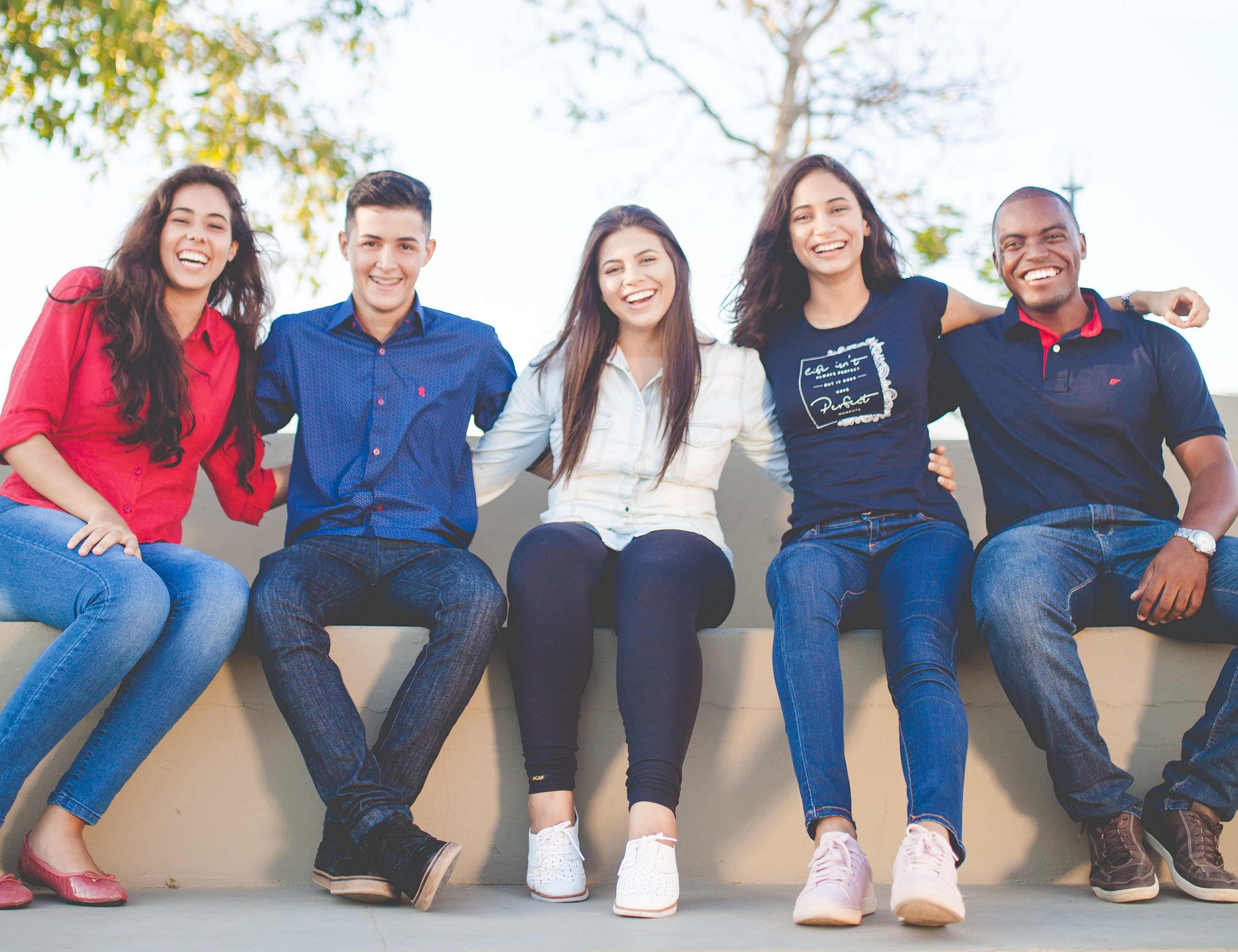 Group of 5 students sitting together and smiling